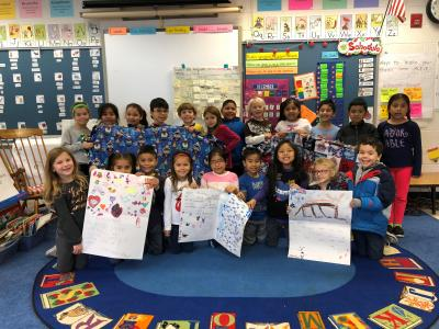 Ms. Zakaria's class holds their finished blanket.